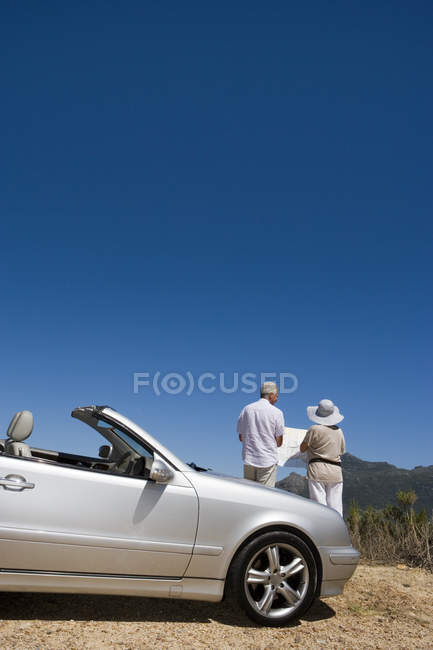 Vue arrière des commandes de couple de personnes âgées en voiture détenant la carte — Photo de stock