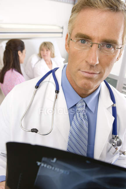 Mature male doctor loking over x ray — Stock Photo