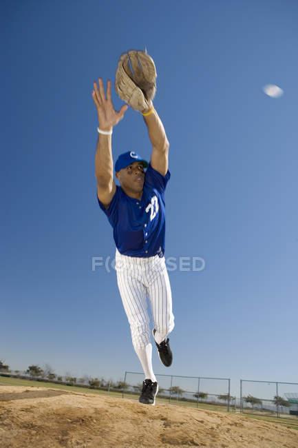 Jugador de béisbol en uniforme azul buceo para atrapar la pelota de guante  protector durante el juego — captura de c4f731e9de0