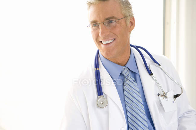 Smiling mature male doctor with stethoscope — Stock Photo