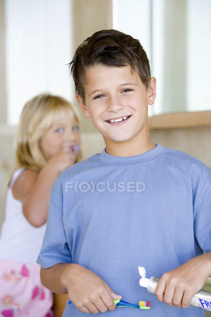 Boy applying toothpaste on brush in bathroom with girl brushing teeth in background — Stock Photo