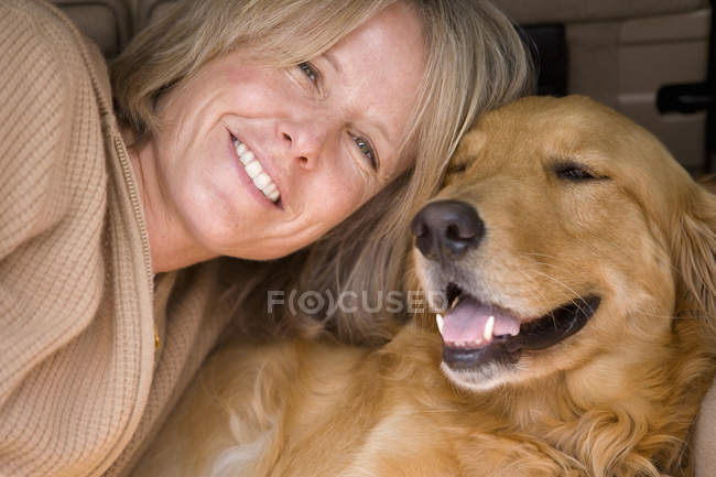 Vue de face de femme se penchant affectueusement contre golden retriever — Photo de stock