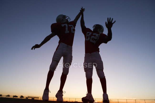 Два гравці американського футболу святкування на полі на заході сонця — стокове фото