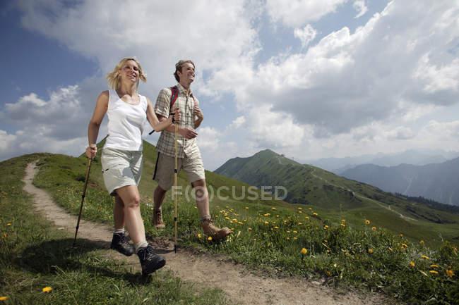 Vista de ângulo baixo de casal com mochilas caminhadas na trilha de montanha — Fotografia de Stock