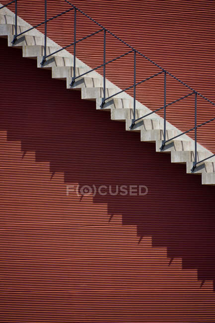 Grey stairs passage making shadow on red facade — Stock Photo