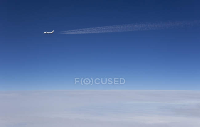Distant view of airplane flying above clouds in gradient blue sky — Stock Photo