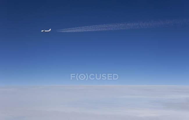 Далеких подання літачок пролітає над хмарами у градієнта Синє небо — стокове фото