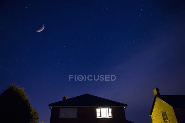 Casas y el cielo nocturno con la luna - foto de stock