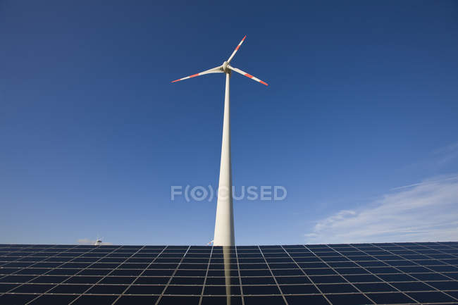 Wind turbine above solar batteries panel on background of gradient blue sky — Stock Photo