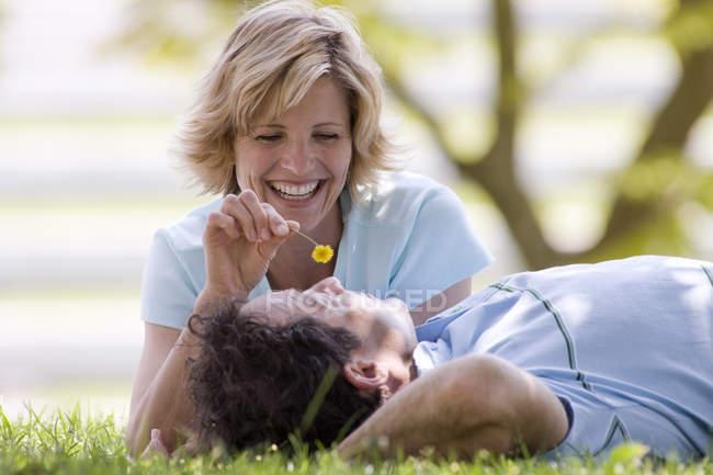 Vista frontale della coppia sdraiata sull'erba con sfondo sfuocato — Foto stock