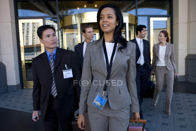 Group of business people exiting building — Stock Photo