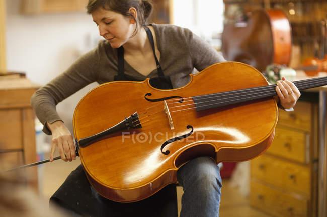 Luthier en vérifiant le violoncelle en atelier — Photo de stock