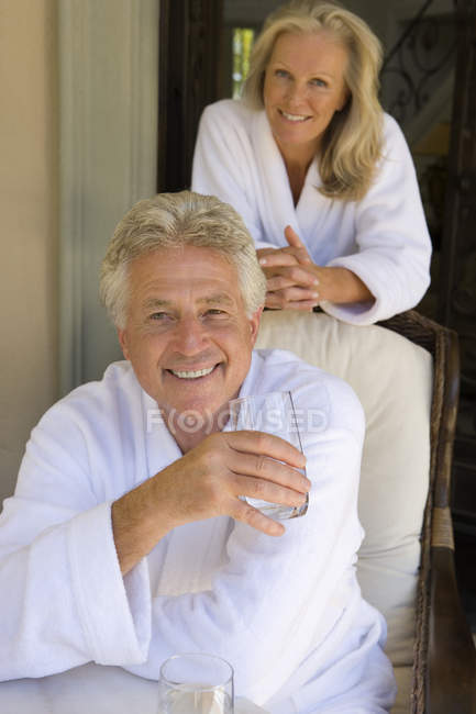 Couple wearing white bathrobes and looking at camera — Stock Photo