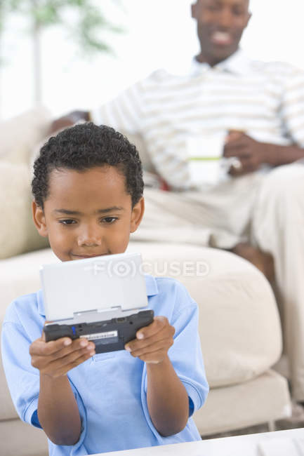 Boy (6-8) playing computer game, father in background — Stock Photo