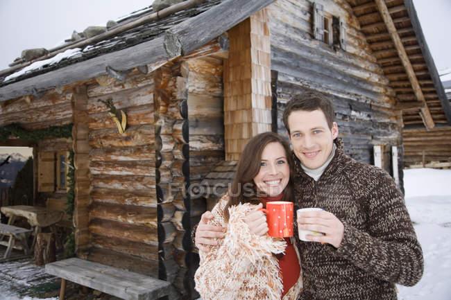 Paar mit Tee vor chalet — Stockfoto