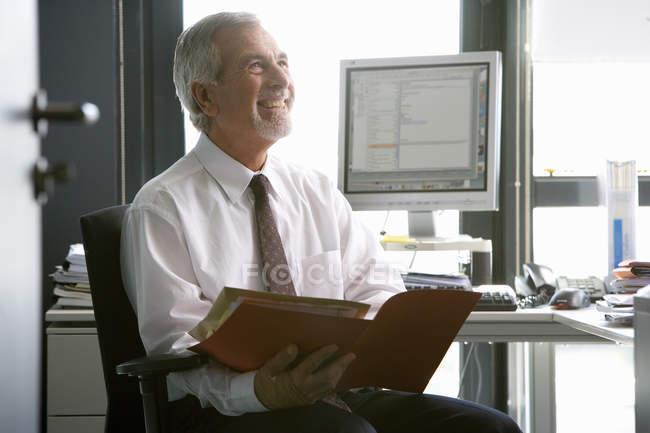 Homem de negócios sênior, revendo a papelada no escritório — Fotografia de Stock
