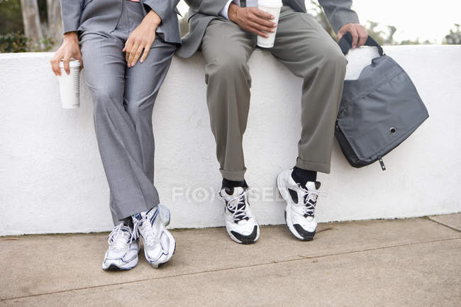 Low section view of businessmen in sports shoes sitting on parapet and drinking coffe — Stock Photo