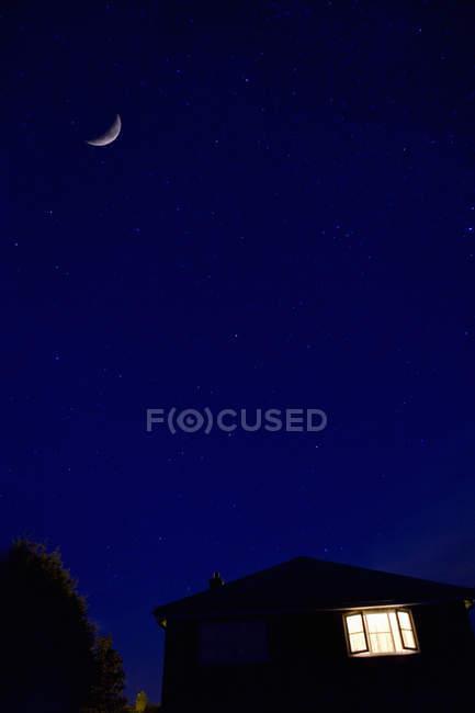 Cielo de la casa y de la noche con la luna - foto de stock