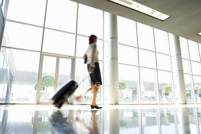 Inquadratura dal basso della donna di affari con bagagli con sfondo sfuocato — Foto stock