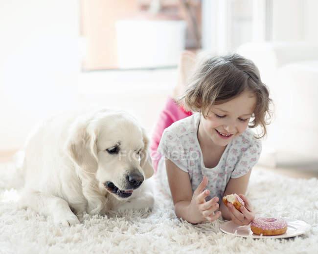 Vista frontal da menina deitada no tapete e comendo rosquinhas ao lado do cão — Fotografia de Stock