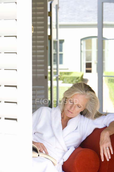 Woman reading book while sitting on sofa — Stock Photo