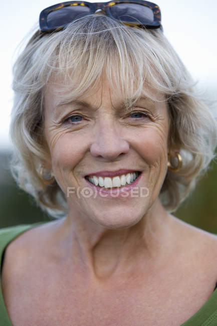 Portrait of smiling mature woman with blurred background — Stock Photo