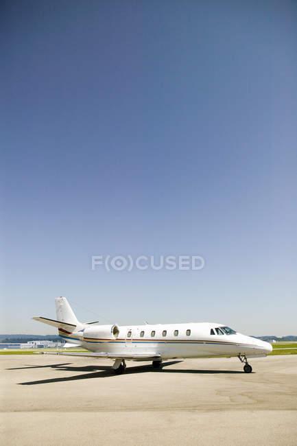 Частный самолет на взлетно-посадочной полосы в аэропорту на Солнечный день — стоковое фото