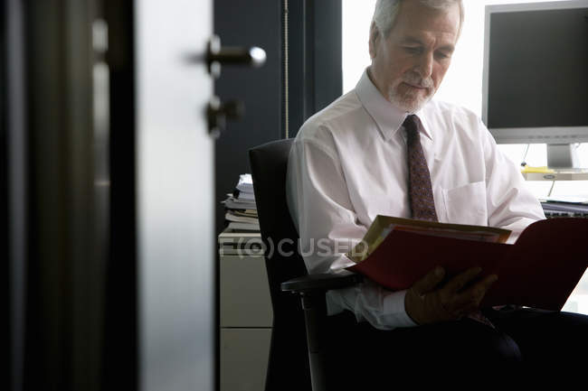 Senior businessman reviewing paperwork in office — Stock Photo