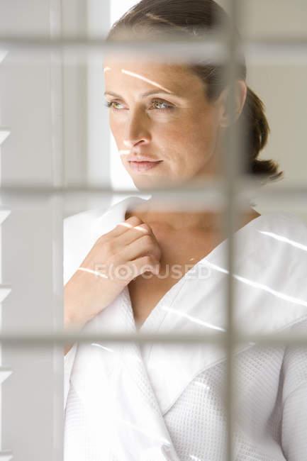 Женщина в Халат, вид через жалюзи — стоковое фото