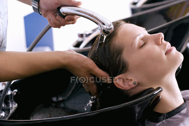 Stylist washing hair of female client with closed eyes in hair salon — Stock Photo