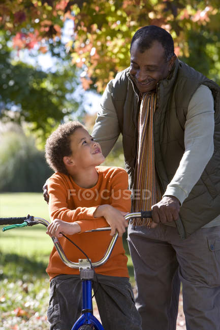 Grandfather helping grandson learn to ride bicycle — Stockfoto