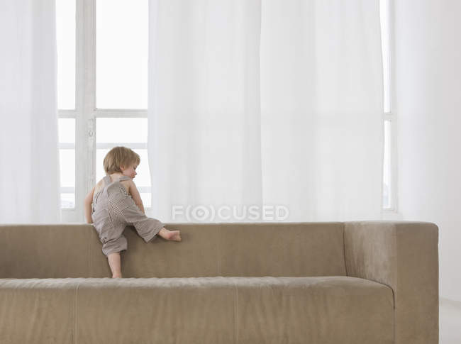 Little boy climbing over back of sofa — Stock Photo