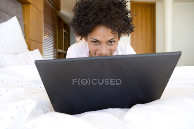 Woman in bed looking over laptop — Stock Photo