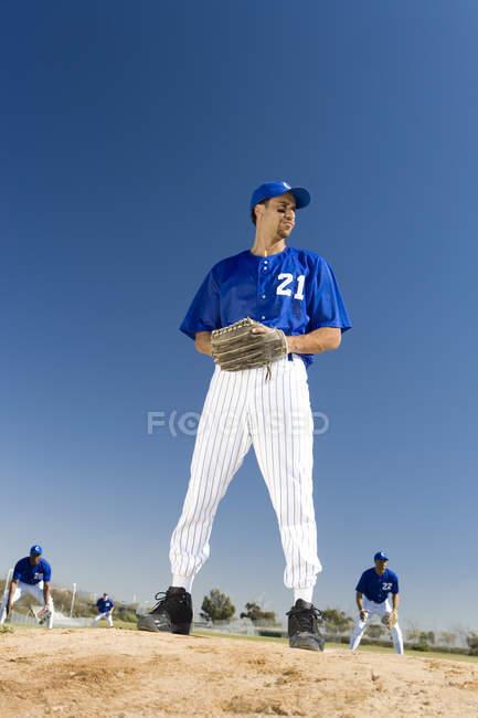 Бейсбол глечик в синій парадний, готується кинути м'яч під час конкурентоспроможної гри — стокове фото