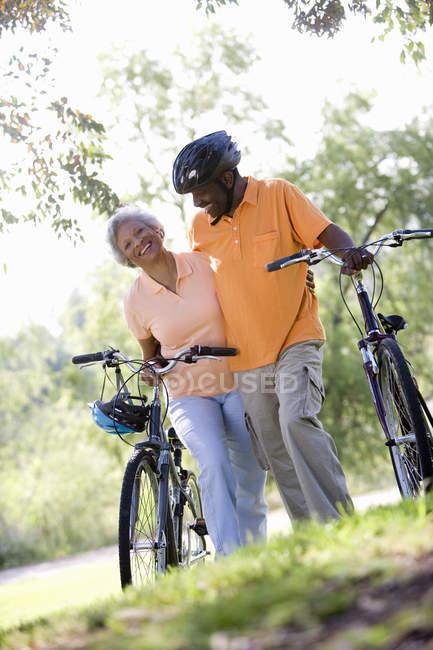 Vista de ángulo bajo de par alto con bicicletas al aire libre - foto de stock