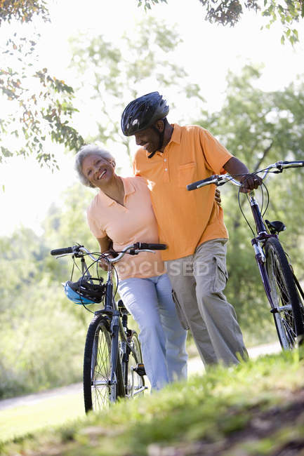 Low angle view of senior couple with bicycles outdoors — Stock Photo