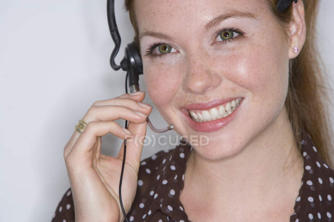 Woman adjusting headset — Stock Photo
