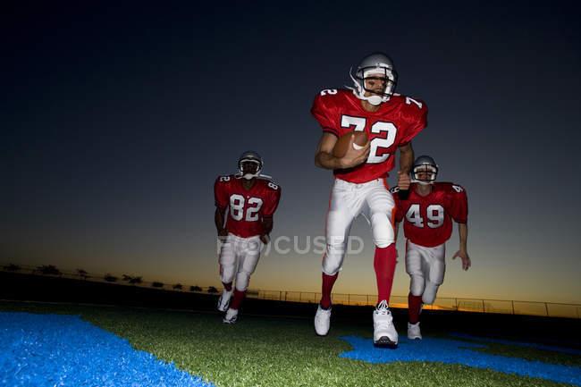 Drei American-Football-Spieler in roten Streifen läuft auf Platz mit Ball bei Sonnenuntergang — Stockfoto