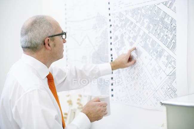 Man pointing at map on wall — Stock Photo