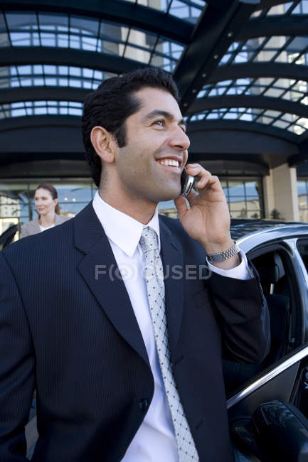 Businessman talking on cell phone in urban setting — Stockfoto
