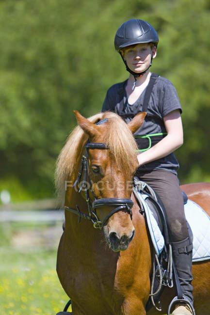 Equitazione di ragazzo in campagna con sfondo sfuocato — Foto stock