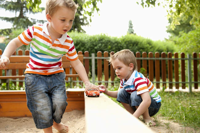 Twin brothers playing in sandpit with toys cars — Stock Photo