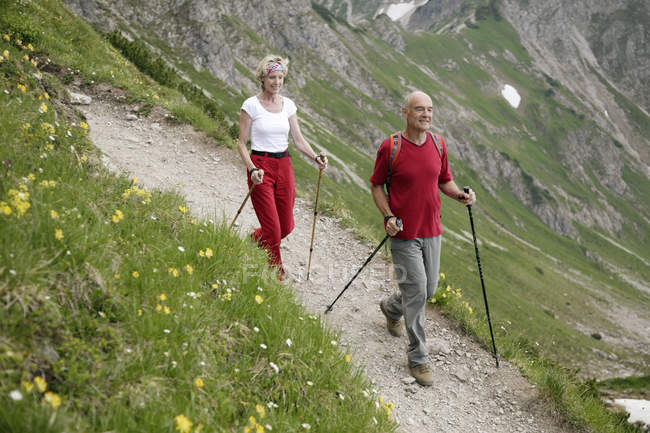 Senior couple with rucksacks hiking on mountain trail — Stock Photo