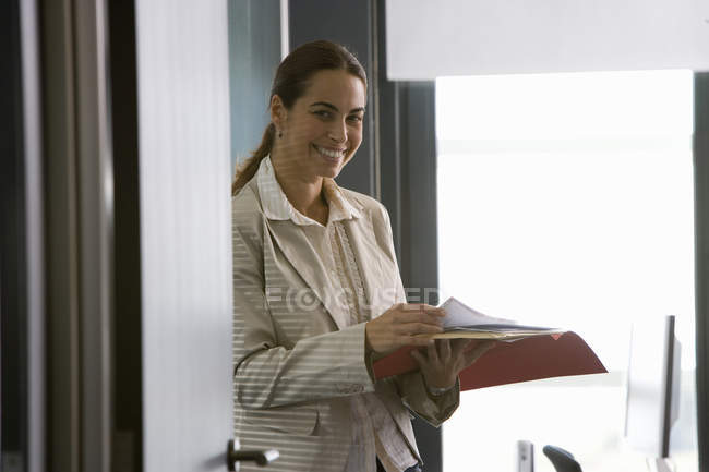 Front view of businesswoman reviewing paperwork in office — Stock Photo