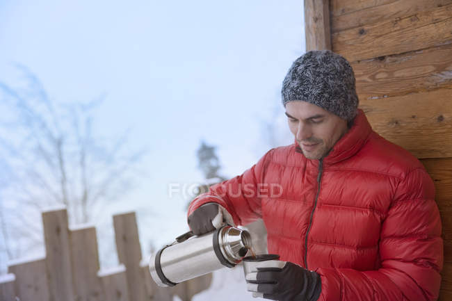Mid adult man pouring drink from flask — Stock Photo