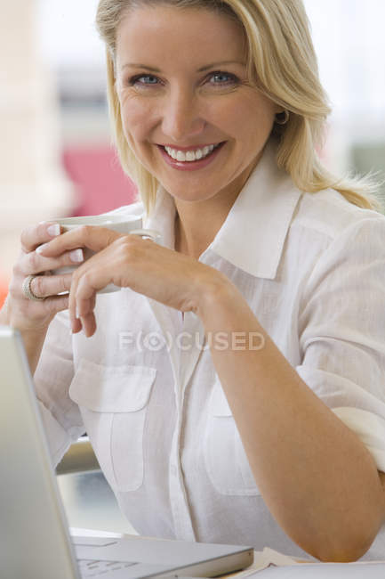 Front view of woman with laptop computer looking at camera — Stock Photo