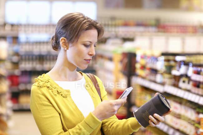 Жінка сканування штрих код в органічних продуктовий магазин — стокове фото