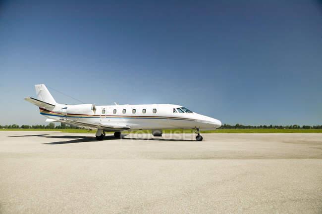 Современный частный самолет на взлетно-посадочной полосы в аэропорту на Солнечный день — стоковое фото