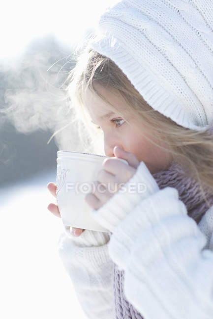 Young girl drinking from mug in winter — Stock Photo