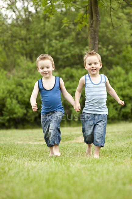 Mano nella mano nel parco, di fratelli gemelli sorridente — Foto stock